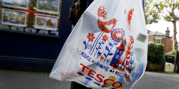 A shopper carries a Tesco supermarket bag in London, Monday, Sept. 22, 2014. Tesco, Britain's largest retailer by revenue, has suspended four executives and launched an accounting investigation after admitting that its half-year profit was overstated by 250 million pounds ($407 million). (AP Photo/Kirsty Wigglesworth)