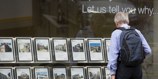 A pedestrian stands beneath a 'Your Property is HOT!' sign as he looks at information leaflets of residential properties displayed for sale in the window of an estate agents in Guildford, U.K., on Monday, June 23, 2014. As Britons brace for the Bank of England to announce steps to restrain the housing market this week, Chief Secretary to the Treasury Danny Alexander dismissed talk of a bubble. Photographer: Jason Alden/Bloomberg via Getty Images