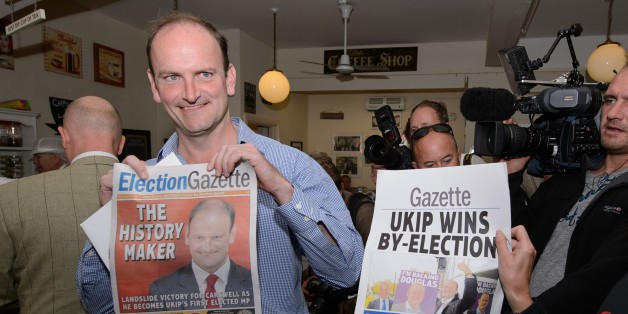 Newly-elected UK Independence Party (UKIP) MP Douglas Carswell (L) poses for photographers with a copy of the local paper in Clacton-on-Sea, in eastern England, on October 10, 2014. Britain's anti-EU UK Independence Party won its first seat in the House of Commons Friday, sending jitters through Prime Minister David Cameron's Conservatives seven months before what is likely to be a tight general election. AFP PHOTO / LEON NEAL        (Photo credit should read LEON NEAL/AFP/Getty Images)