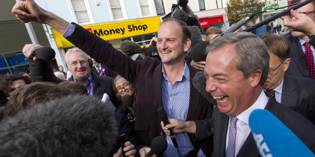 Newly elected UK Independence Party (UKIP) MP Douglas Carswell (C) and party leader Nigel Farage (R) are pictured as they celebrate in Clacton-on-Sea, in eastern England, on October 10, 2014. Britain's anti-EU UK Independence Party won its first seat in the House of Commons Friday, sending jitters through Prime Minister David Cameron's Conservatives seven months before what is likely to be a tight general election. AFP PHOTO / JUSTIN TALLIS        (Photo credit should read JUSTIN TALLIS/AFP/Gett