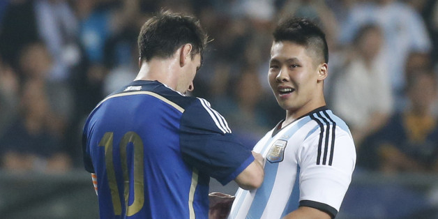 Argentina's Lionel Messi, left, signs an autograph for a supporter after the supporter ran onto the pitch past security officers during a friendly soccer match against Hong Kong in Hong Kong Tuesday, Oct. 14, 2014. (AP Photo/Kin Cheung)