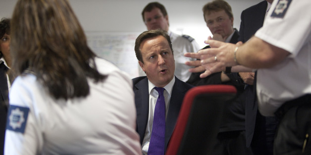 Britain's Prime Minister David Cameron talks with United Kingdom Border Agency officials in their control room, during a visit to Terminal 5 at London's Heathrow airport, Monday Oct. 10, 2011. Cameron met border staff and viewed the latest facial recognition technology used at passport control, ahead of a major speech on immigration. Around 150 people are refused entry to the United Kingdom each week, and about 350 are stopped for questioning.(AP Photo/Richard Pohle, pool)