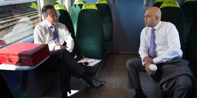 Prime Minister David Cameron and Sajid Javid, secretary of state for culture media and sport as they travel by train to Purfleet in Essex where they met apprentices at the Royal Opera House Production Workshop who make scenery for the famous theatre in London.