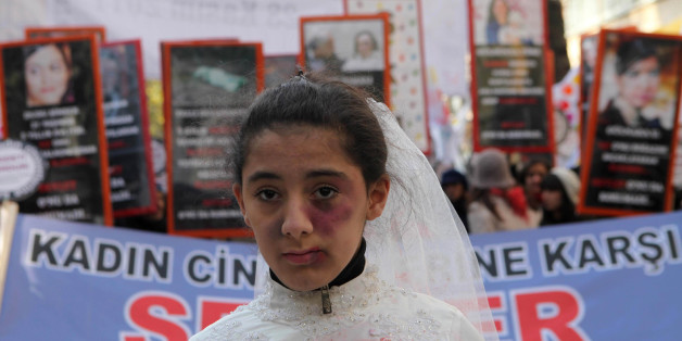 A Turkish girl, wearing a wedding dress and covered with fake bruises, stands in front of other protesters holding placard reading '' end violence'' during a demonstration to protest against rape, killings and domestic violence against women, in Ankara on November 27, 2011. AFP PHOTO/ADEM ALTAN (Photo credit should read ADEM ALTAN/AFP/Getty Images)