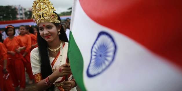 "A school student dressed as ""Mother India"" holds an Indian flag during Independence Day celebrations in Gauhati, India, Friday Aug. 15 2014. India celebrates its 1947 independence from British colonial rule on Aug. 15. (AP Photo/Anupam Nath)"