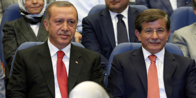 Turkey's president-elect Recep Tayyip Erdogan, left, and Foreign Minister Ahmet Davutoglu sit together during a party meeting in Ankara, Turkey, Thursday, Aug. 21, 2014. Davutoglu, hand-picked by Erdogan to succeed him as prime minister, is widely expected to accept a backseat role as his boss strives to make his new job the most powerful position in the land.(AP Photo/Burhan Ozbilici)