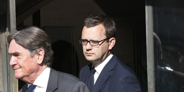 Andy Coulson, background, former News of the World editor leaves the Central Criminal Court in London, Tuesday, June 24, 2014. Coulson was convicted of phone hacking Tuesday, but fellow editor Rebekah Brooks was acquitted after a trial centering on illegal activity at the heart of Rupert Murdoch's newspaper empire. A jury at London's Old Bailey unanimously found Coulson, the former spin doctor of British Prime Minister David Cameron, guilty of conspiring to intercept communications. Brooks was acquitted of that charge and of counts of bribing officials and obstructing police. The nearly eight-month trial was triggered by revelations that for years the News of the World used illegal eavesdropping to get stories, listening in on the voicemails of celebrities, politicians and even crime victims. (AP Photo/Lefteris Pitarakis)