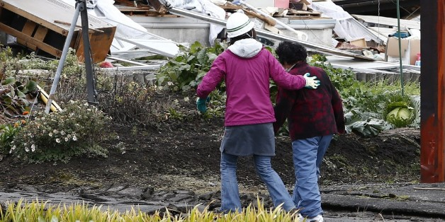 Local residents walk past a collapsed house after a strong earthquake hit the area the night before, in Hakuba, some 300 kms northwest of Tokyo, Nagano prefecture, on November 23, 2014. A strong 6.2 magnitude earthquake, which hit late on November 22 in central Japan, left 39 people injured, seven seriously, and wrecked homes in a popular ski resort.  JAPAN OUT       AFP PHOTO/Jiji Press              (Photo credit should read JIJI PRESS/AFP/Getty Images)