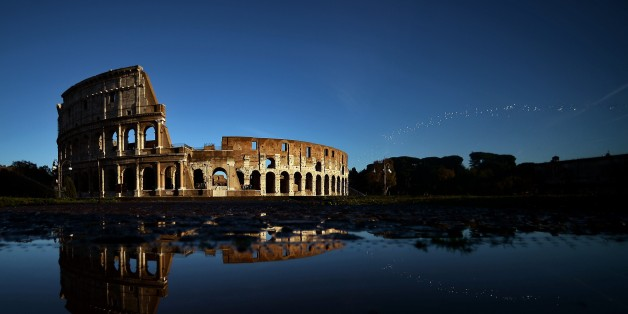 The Colosseum reflects in the water on November 21, 2014 in Rome.  AFP PHOTO / FILIPPO MONTEFORTE        (Photo credit should read FILIPPO MONTEFORTE/AFP/Getty Images)