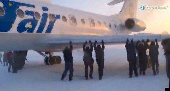 passengers push frozen plane