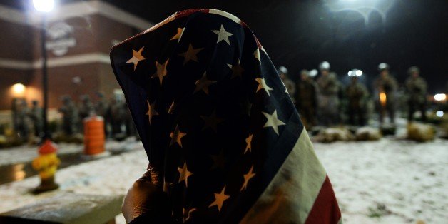 A demonstrator covers himself with a US flag as he joins other to protest outside the police station in Ferguson, Missouri, on November 26, 2014. The streets of Ferguson were decidedly calmer on November 26 after two days of nationwide protests against the decision not to prosecute a white policeman who shot dead an unarmed black teenager. Just a few dozen protesters and clergy braved rain and light snow to protest outside the police department in the St Louis suburb, where 18-year-old Michael B