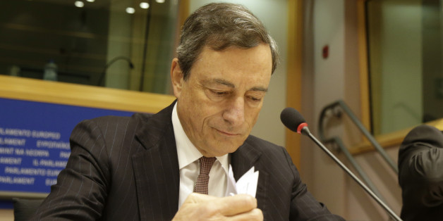 President of the European Central Bank Mario Draghi checks his papers prior to address the Committee on Economic and Monetary Affairs, at the European Parliament building, in Brussels on Monday, Nov. 17, 2014. (AP Photo/Yves Logghe)