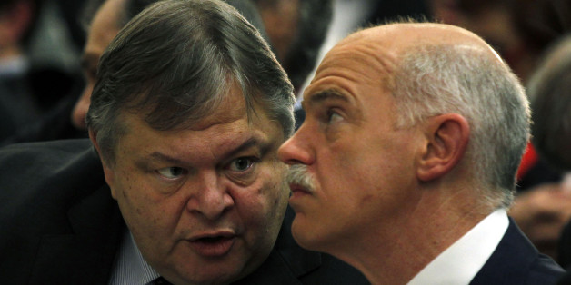Greeces' Finance Minister Evangelos Venizelos, left, speaks to former Greek Prime Minister George Papandreou during a conference of PASOK socialist party at Faliro near Athens, Saturday, March 10, 2012. Greece's private creditors agreed Friday to take cents on the euro in the biggest debt writedown in history, paving the way for an enormous second bailout for the country to keep Europe's economy from being dragged further into chaos. (AP Photo/Kostas Tsironis)