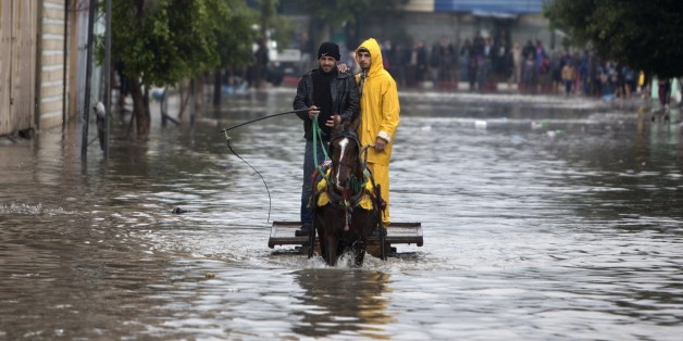 Palestinian men in a horse cart make their way through a flooded street during heavy rains in Gaza City on November 27, 2014 as a fierce winter storm which has been battering the region for the past four days. AFP PHOTO /MAHMUD HAMS        (Photo credit should read MAHMUD HAMS/AFP/Getty Images)