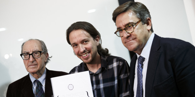 Pablo Iglesias, Secretary General of 'Podemos' ('We can'), center, poses as he holds 'An Economic Project for the People' written by Spanish economists Vincenc Navarro, left, and Juan Torres, right, in Madrid, Spain, Thursday, Nov. 27, 2014. Latest polls show the recently-formed Spanish party 'Podemos' has risen to become the most popular choice among Spanish voters for the general elections to be held in 2015. (AP Photo/Daniel Ochoa de Olza)