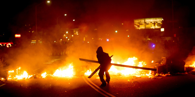 A protester adds wood to a fire burning in Oakland, Calif., on Tuesday, Nov. 25, 2014, a day after the announcement that a grand jury decided not to indict Ferguson police officer Darren Wilson in the fatal shooting of Michael Brown. Protesters briefly shut down two major freeways, vandalized police cars and looted businesses in downtown Oakland, smashing windows at cell phone stores, car dealerships, restaurants and convenience stores on a second night of protests. (AP Photo/Noah Berger)