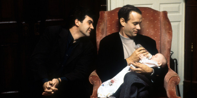Tom Hanks feeds a baby while Antonio Banderas watches in a scene from the film 'Philadelphia', 1994. (Photo by TriStar/Getty Images)