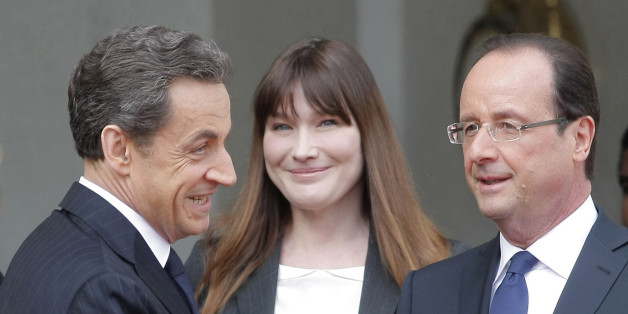 FILE - This May 15, 2012 photo from files shows the then new French President, Francois Hollande, right, shaking hand with outgoing President Nicolas Sarkozy while Hollande's companion Valerie Trierweiler, behind left, and Carla Bruni-Sarkozy, behind center, look on,  after the handover ceremony at the Elysee Palace in Paris. Former French First Lady Carla Bruni says she thinks her unmarried successor Valerie Trierweiler should get hitched to be taken more seriously. (AP Photo/Thibault Camus, File)