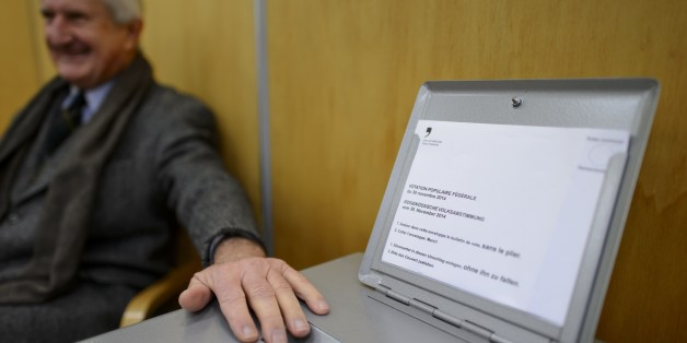 An usher guards the ballot box on November 30, 2014 in the old town of Fribourg. The Swiss voted early Sunday in three national referendums, including one calling for dramatic immigration cuts in the name of saving the environment, in polling open for just two hours. Most voters, however, had already cast their ballots by mail, and initial results were expected to be available shortly after polling stations closed at noon.  AFP PHOTO / FABRICE COFFRINI        (Photo credit should read FABRICE CO