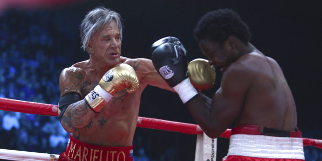 US actor Mickey Rourke, left, punches his opponent Elliot Seymour of the United States, during their professional boxing match at the Luzhniki Stadium, in Moscow, Russia, on Friday, Nov. 28, 2014. Hollywood actor Mickey Rourke returned to the boxing ring Friday at the age of 62, defeating a fighter less than half his age in an exhibition bout. (AP Photo/Denis Tyrin)