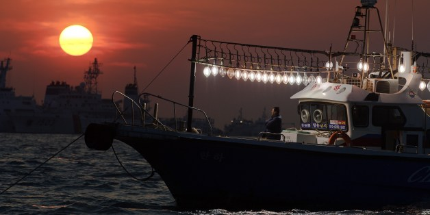 A man stands on a fishing boat using its lights to help illuminate an area of recovery operations at the site of the submerged 'Seowl' ferry off the coast of the South Korean island of Jindo on April 24, 2014. The confirmed death toll from South Korea's ferry disaster rose  sharply to more than 120 on April 22, as divers speeded up the grim task of recovering bodies from the submerged ship and police took two more of its crew into custody. AFP PHOTO/ Nicolas ASFOURI        (Photo credit should r