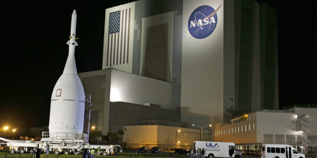 The Orion Spacecraft moves by the Vehicle Assembly Building on its approximately 22 mile journey from the Launch Abort System Facility at the Kennedy Space Center to Space Launch Complex 37B at the Cape Canaveral Air Force Station, Tuesday, Nov. 11, 2014, in Cape Canaveral, Fla. The test flight for Orion is scheduled to launch on Dec. 4.(AP Photo/John Raoux)