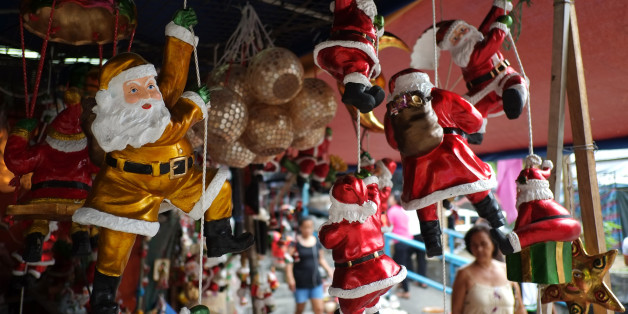 A Filipino woman looks at Santa Claus figurines outside makeshift stalls as people begin shopping for Christmas decorations for their homes in Manila, Philippines, Thursday, Nov. 20, 2014. Christmas is one of the most important holidays in this predominantly Roman Catholic nation. (AP Photo/Aaron Favila)