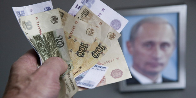 GERMANY, BONN - DECEMBER 02:Hand with russian ruble banknotes and a framed Putin photo in the background, on December 02, 2014 in Bonn, Germany. (Photo by Ulrich Baumgarten via Getty Images)