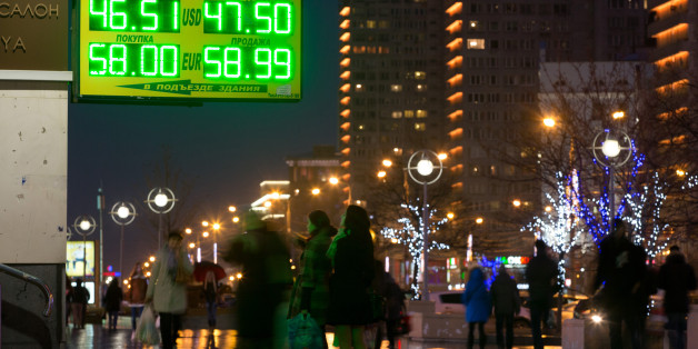 Pedestrians pass illuminated rates for dollar and euro currencies against the ruble on an electronic sign outside a currency exchange bureau near residential apartment blocks in Moscow, Russia, on Sunday, Nov. 9, 2014. The ruble has lost more than 28 percent against the dollar so far this year, the second-worst performance among more than 170 currencies tracked by Bloomberg. Photographer: Andrey Rudakov/Bloomberg via Getty Images