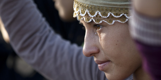 A girl cries during the funeral of 19 year-old Syrian Kurdish fighter girl Perwin Mustafa Dihap who died after being wounded during fighting against the Islamic State forces in her home town of Kobani, in Suruc, on the Turkey-Syria border Friday, Nov. 7, 2014. Kobani, also known as Ayn Arab, and its surrounding areas, has been under assault by extremists of the Islamic State group since mid-September and is being defended by Kurdish fighters. (AP Photo/Vadim Ghirda)