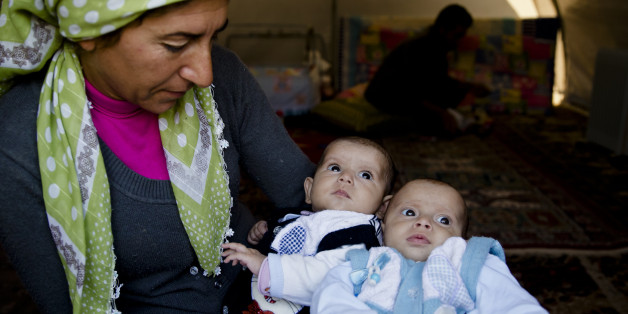 A Syrian Kurdish refugee woman from the Kobani area holds two babies at a camp in Suruc, on the Turkey-Syria border Wednesday, Nov. 19, 2014. Kobani, also known as Ayn Arab, and its surrounding areas, has been under assault by extremists of the Islamic State group since mid-September and is being defended by Kurdish fighters. (AP Photo/Vadim Ghirda)