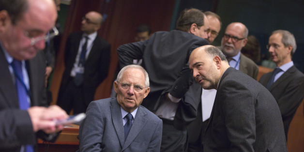 European Commissioner for Economic and Financial Affairs Pierre Moscovici, center right, speaks with German Finance Minister Wolfgang Schaeuble, center left, during a meeting of the eurogroup finance ministers at the EU Council building in Brussels on Monday, Dec. 8, 2014. (AP Photo/Virginia Mayo)