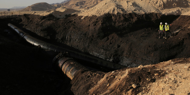 Employees of the Trans-Israel Pipeline clean up the large deposits of crude oil that gushed out of a breached pipeline near the southern Israeli village of Beer Ora, north of Eilat, Friday, Dec. 5, 2014. Israel says a breached pipeline has caused a large oil spill in the southern part of the country. The spill occurred when the pipeline, linking Eilat to the port city of Ashkelon on the Mediterranean Sea, burst. The spill occurred in a dramatic desert landscape featuring steeply rising cliffs ne