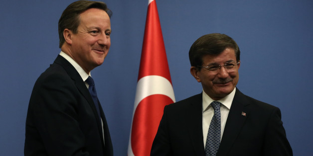British Prime Minister David Cameron, left, and his Turkish counterpart Ahmet Davutoglu shake hands after a news conference in Ankara, Turkey, Tuesday, Dec. 9, 2014. Cameron also met President Recep Tayyip Erdogan and discussions are likely to focus on the fight against Islamic State group in Syria and Iraq. Cameron is expected to bring up the problem of British citizens entering Turkey in order to join IS group in Syria and Iraq.(AP Photo/Burhan Ozbilici)