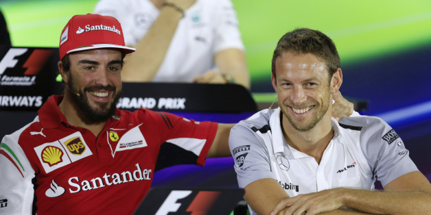 Ferrari driver Fernando Alonso of Spain, left, and McLaren Mercedes driver Jenson Button of Britain share a lighter moment during a news conference at the Yas Marina racetrack in Abu Dhabi, United Arab Emirates, Thursday, Nov. 20, 2014. With double points on offer in the Formula One finale, there could yet be a bitter twist to the fascinating title duel between Mercedes teammates Lewis Hamilton and Nico Rosberg at the Abu Dhabi Grand Prix. The Emirates Formula One Grand Prix will take place on Sunday. (AP Photo/Hassan Ammar)