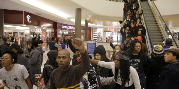 Protesters march inside Chesterfield Mall Friday, Nov. 28, 2014, in Chesterfield, Mo. The crowd disrupted holiday shopping at several locations on Friday amid a protest triggered by a grand jury's decision not to indict the police officer who fatally shot Michael Brown in nearby Ferguson. (AP Photo/Jeff Roberson)