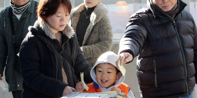 A boy (C) helps his mother (L) to cast a vote in Japan's general election at a polling station in Tokyo on December 14, 2014. Japanese voters went to the polls for a general election likely to return Prime Minister Shinzo Abe to power, and billed as a referendum on his economic policy. Polling stations opened early across the nation in a lower house election with 1,191 candidates vying for 475 seats.  AFP PHOTO / Yoshikazu TSUNO        (Photo credit should read YOSHIKAZU TSUNO/AFP/Getty Images)