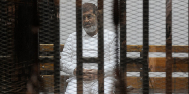CAIRO, EGYPT - NOVEMBER 5: Ousted Egyptian president Mohammed Morsi looks from behind defendants cage bars during his trial in Cairo, Egypt on November 5, 2014. According to reports, Morsi is standing trial with other defendants from his administration and Muslim Brotherhood for allegedly inciting Islamist supporters to kill anti-Islamist protesters outside the presidential palace in December 2012. (Photo by Stringer/Anadolu Agency/Getty Images)