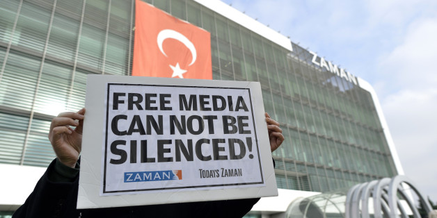 A man holds a placard as people gather in support outside Zaman newspaper in Istanbul, Turkey, Sunday, Dec. 14, 2014, hours after police launched raids in a dozen cities, detaining at least 23 people, including journalists, television producers and police known to be close to a movement led by a U.S.-based moderate Islamic cleric Fethullah Gulen. The government accuses the Gulen's movement, a former ally, of orchestrating an alleged plot to try and bring down the government. It says the group's