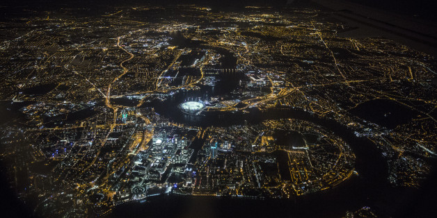 LONDON, ENGLAND - MAY 20:  An aerial view of the buildings and streets of London, including the O2 Arena and the Canary Wharf development on the Isle of Dogs, which are illuminated at night on May 20, 2014 in London, England. (Photo by Oli Scarff/Getty Images)