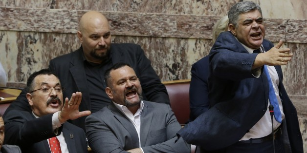 The leader of the far-right political party, Golden Dawn, Nikos Michaloliakos, right, lawmakers Christos Pappas, left, and Yannis Lagos react against Parliament members in Athens, Wednesday, June 4, 2014. Michaloliakos, Pappas, and Lagos were transferred from prison to parliament to speak during a debate on lifting their immunity on additional weapons charges. (AP Photo/Thanassis Stavrakis)
