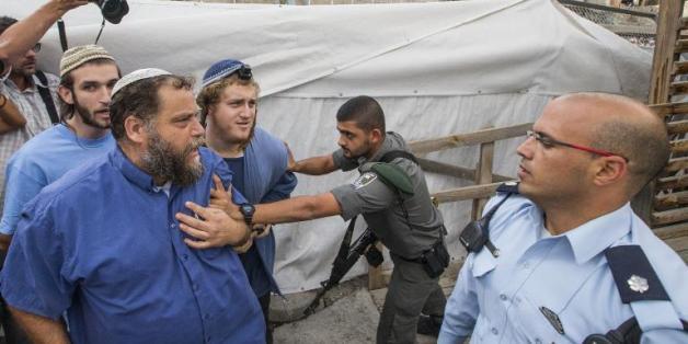 Un garde-frontière repousse des membres de Lehava, dont le chef Bentzi Gopstein (2e à g), qui tentent d'accéder à l'esplanade des Mosquées, temporairement fermée au public, le 30 octobre 2014