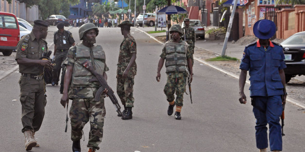 Nigerian soldiers patrol the area,  near the scene of an explosion in Abuja, Nigeria, Wednesday, June 25, 2014. An explosion rocked a shopping mall in Nigeria's capital, Abuja, on Wednesday and police say at least over 20 people have been killed and many wounded. Witnesses say body parts were scattered around the exit to Emab Plaza, in the upscale Wuse 11 suburb. (AP Photo/Olamikan Gbemiga)