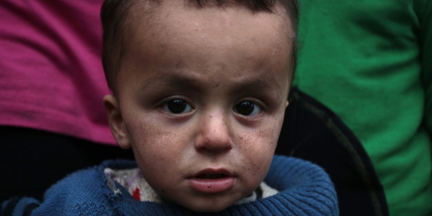 The ash covered face of one-year-old Mayar Abdo from Syrian as he stands with his family near an open fire in front of their unheated tents in a refugee camp in the town of Harmanli, Bulgaria, Thursday, Nov. 21, 2013.  Thousands of Syrian and other refugees from the Middle East, Asia and Africa, who find enough courage to make a dangerous journey from their war-ravaged states, often end up in the crammed settlements in the Balkans, including Bulgaria, Greece or Serbia, after being caught on the borders of wealthy Western European nations for attempting to cross illegally. (AP Photo/Valentina Petrova)