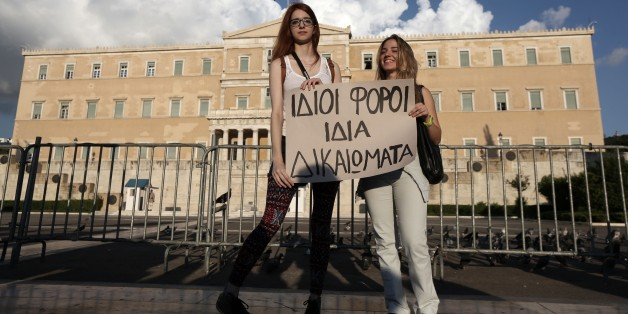 A lesbian couple Christina, left, and Ioanna hold a banner that reads ''Same taxes, same rights'' during a protest outside Greece's Parliament in Athens on Friday, Sept. 5, 2014. Several hundred people took part in the peaceful march to Parliament, which is debating draft legislation to outlaw Holocaust denial and expand prosecution powers against the incitement of racial violence. Gay and Lesbian rights groups complain that the proposed legislation will not adequately address attacks on homosexual people, which they say are on the rise. (AP Photo/Thanassis Stavrakis)