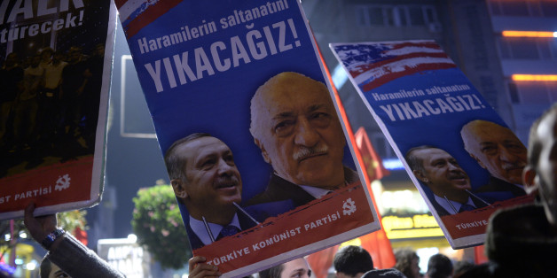 A Turkish protester holds up a placard with pictures of Turkish Prime Minister Recep Tayyip Erdogan (L) and the United States-based Turkish cleric Fethullah Gulen reading 'We will cast them down' during a demonstration against corruption in the Kadikoy district of Istanbul on December 25, 2013. Turkish Prime Minister Recep Tayyip Erdogan replaced nearly half his cabinet in a dramatic reshuffle late on December 25 after a spreading graft scandal forced the resignation of three top ministers and t