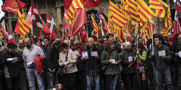 Pro-independence demonstrators of Catalonia and Basque Country raise their regional flags as they gather on a square to support an informal independence poll to celebrate in Catalonia, in Pamplona northern Spain, Sunday, Nov. 9, 2014. The pro-independence regional government of Catalonia stages a symbolic poll on secession in a show of determination and defiance after the Constitutional Court suspended its plans to hold an official independence referendum following a legal challenge by the Spanish government.  (AP Photo/Alvaro Barrientos)