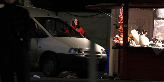 A police officer stands by the van that crashed into a French Christmas market in Nantes, western France, Monday, Dec.22, 2014. French authorities urged calm after a series of attacks across the country left dozens of people injured, and said there was no evidence the attacks were connected by any terrorist motive. In the latest incident, 11 people were injured after a driver crashed his van into a crowded Christmas market in western France Monday evening. The driver then stabbed himself several times and is among five people hospitalized in serious condition, authorities said. (AP Photo/Laetitia Notarianni)
