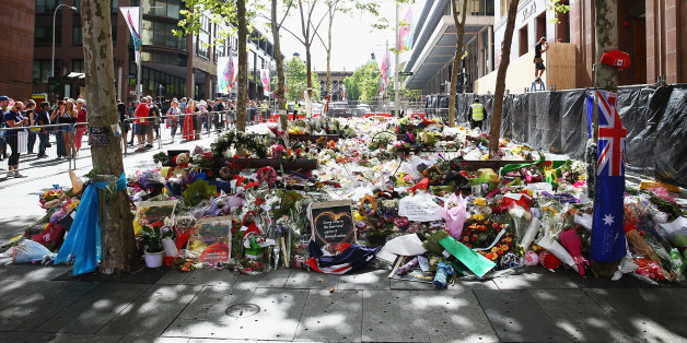 SYDNEY, AUSTRALIA - DECEMBER 23:  Flowers can been seen outside the Lindt cafe just prior to being removed at Martin Place on December 23, 2014 in Sydney, Australia. Volunteers have gathered at Martin Place this morning to begin clearing the thousands of bouquets and cards left in tribute to Tori Johnnson and Katrina Dawson, who were killed in last week's hostage siege at the Lindt Cafe.  (Photo by Don Arnold/Getty Images)
