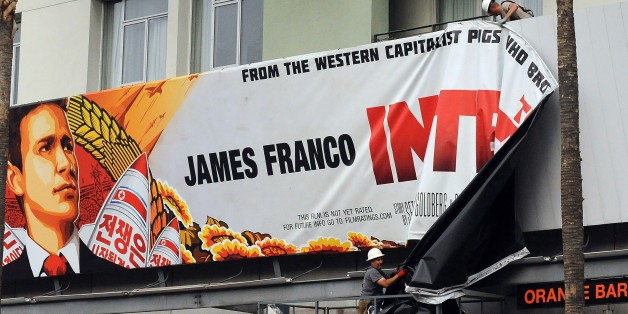 Workers remove a poster for 'The Interview' from a billboard in Hollywood, California, December 18, 2014 a day after Sony announced it had no choice but to cancel the movie's Christmas release and pull it from theaters due to a credible threat.  Sony defended itself Thursday against a flood of criticism for canceling the movie which angered North Korea and triggered a massive cyber-attack, as the crisis took a wider diplomatic turn.   AFP PHOTO / MICHAEL THURSTON        (Photo credit should read